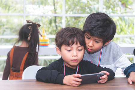 Photo for Two Little boys are playing online game on mobile phone - Royalty Free Image