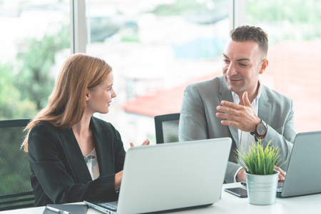 Photo for Male boss is discussing with female worker in happy manner - Royalty Free Image