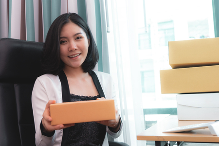 Foto de Start up business woman is holding delivery boxes ready to send out to customer - Imagen libre de derechos