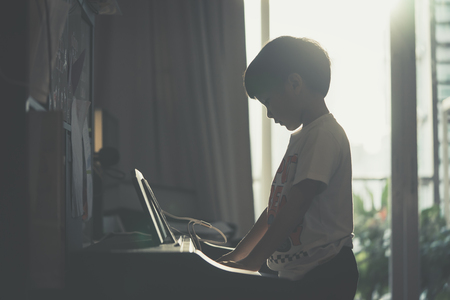 Photo for Little Boy is playing with piano and Music Tablet at home - Royalty Free Image