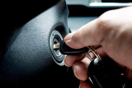 Photo pour Hand turning car key in the key hole to start the car engine - image libre de droit