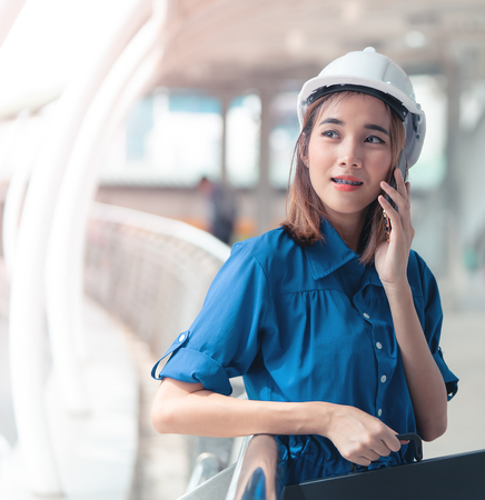 Photo for Young engineer woman is calling mobile in a modern city - Royalty Free Image