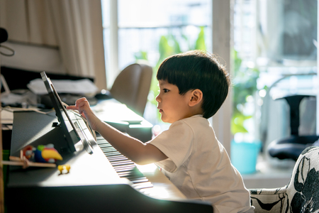 Foto de Little Boy is playing with piano and Music Tablet at home - Imagen libre de derechos