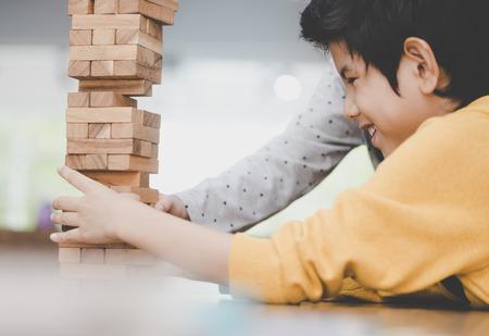 Photo pour Boy is building toy block tower with friend - image libre de droit