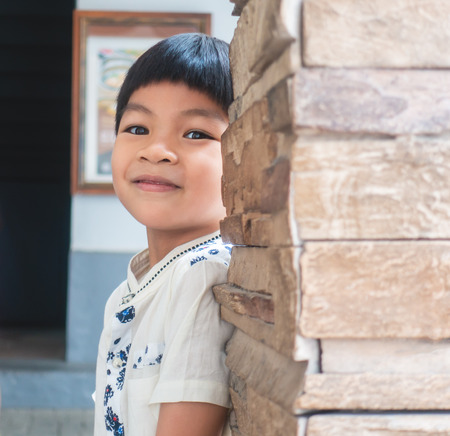 Photo for Asian Kid Hiding behind the stone pole - Royalty Free Image