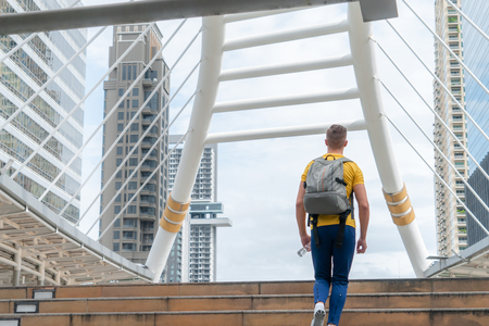 Photo pour Male sport man is walking up the stair in modern city - image libre de droit