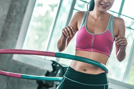 Foto per unrecognized Female in pink sportwear is working out with  in fitness gym for healthy lifestyle concept - Immagine Royalty Free