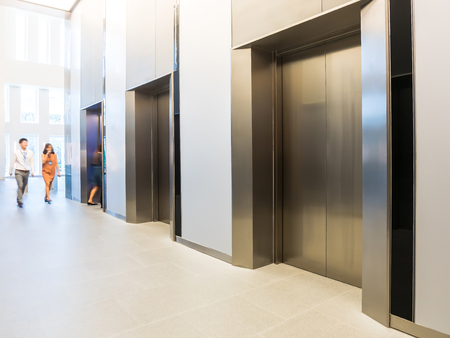 Photo for People are walking in office past elevators, Modern steel elevator cabins in a business lobby or Hotel, Store, interior, office,perspective wide angle. - Royalty Free Image
