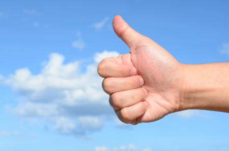 Male hand showing thumb up sign on blue sky background