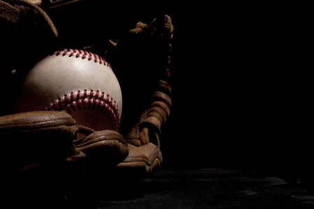 Dramatic lighting of an old baseball and glove isolated on black background