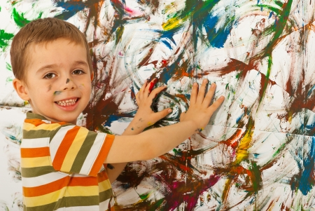 Happy child boy painting a wall with his palms
