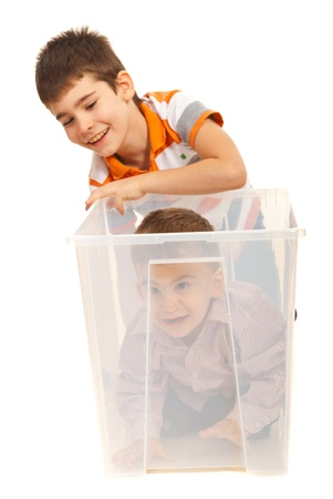 Big brother laughing while his little bro being in a transparent box isolated on white background