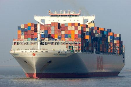 Foto de ANTWERP, BELGIUM - MAR 12, 2016: Container ship OOCL Singapore leaving a container terminal in the Port of Antwerp. - Imagen libre de derechos