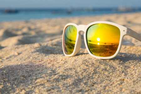 Photo pour Sunrise on a tropical beach reflected in a pair of sunglasses - image libre de droit