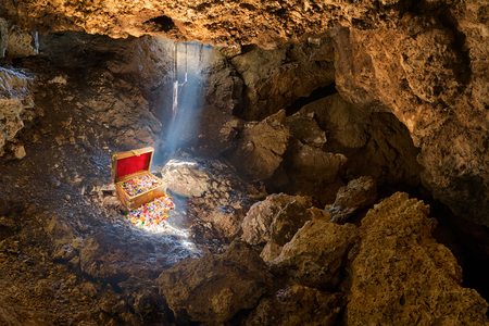 Photo pour Cave with skylight streaming sunlight on a treasure chest - image libre de droit