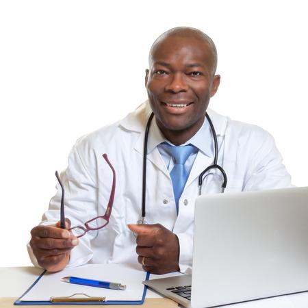 Foto de African doctor on a desk with glasses in his hand - Imagen libre de derechos