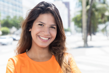 Photo pour Beautiful caucasian woman in a orange shirt in the city - image libre de droit