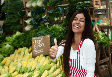 Photo for Laughing latin american saleswoman at farmers market with corn and vegetables - Royalty Free Image