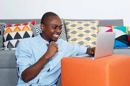 Foto de Successful cheering african american man with computer - Imagen libre de derechos