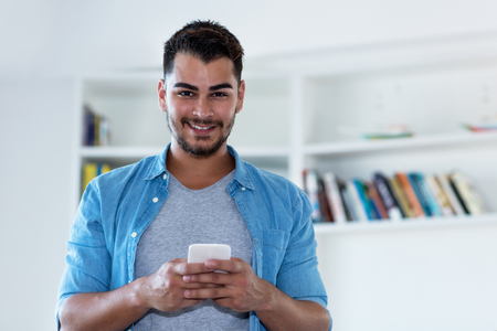 Photo pour Mexican hipster man with beard sending message with phone indoor at home - image libre de droit