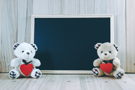Photo pour Lovely couple bear hold the heart near blackboard on the wooden floor, Valentine day concept - image libre de droit