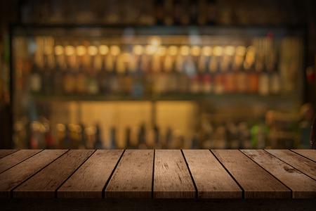 Foto de wooden table with a view of blurred beverages bar backdrop - Imagen libre de derechos