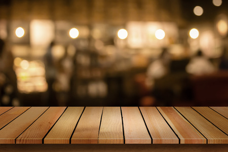 Foto de Wood table top on blur bokeh cafe background can be used for display or montage your products - Imagen libre de derechos