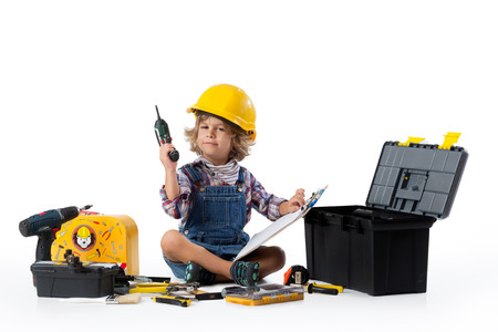 Photo pour Little boy dressed as utility worker with protective helmet trying to figure ou how the drill works - image libre de droit