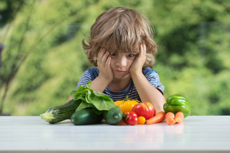 Photo pour Cute little boy sitting at the table, frustrated by vegetable meal, bad eating habits, nutrition and healthy eating concept - image libre de droit