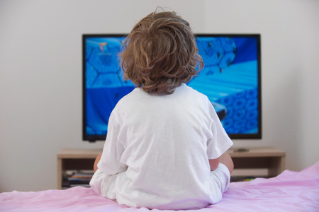 Foto de Little boy sitting on bed watching television. - Imagen libre de derechos