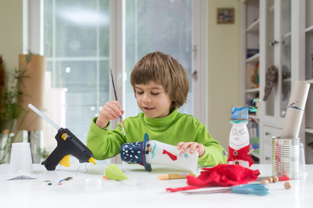 Photo pour Little boy being creative painting dots on homemade do-it-yourself toys made of yogurt bottle and paper. Supporting creativity, hand craft. Creative leisure for children indoors. - image libre de droit