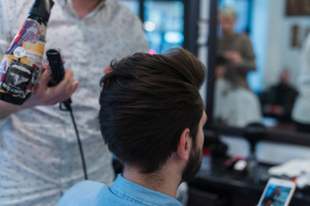 Photo pour Barber shop. Man in barber's chair, hairdresser styling his hair - image libre de droit