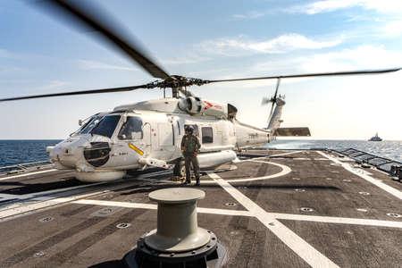 Foto de PHUKET, THAILAND - APRIL 9, 2019:  PHUKET, THAILAND - APRIL 9, 2019:  Sikorsky MH-60S Seahawk helicopter lands on the flight deck of the HTMS. Bhumibol Adulyadej stealth frigate of Royal Thai navy with air operator prepare for take off - Imagen libre de derechos
