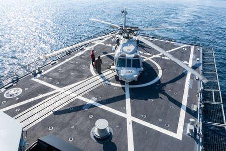 Foto de PHUKET, THAILAND - APRIL 9, 2019:  Sikorsky MH-60S Seahawk helicopter lands on the flight deck of the HTMS. Bhumibol Adulyadej  stealth frigate of Royal Thai navy with fireman prepare for take off. - Imagen libre de derechos