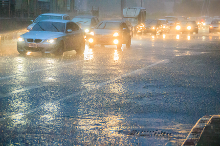 Bangkok, Thailand - July 6. 2017: Driving car through the heavy rain in the evening. Traffic under heavy rain with hail in dangerous situation with low visibility, slippery and splashing water.