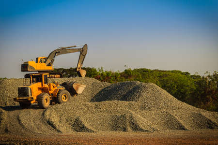 Photo pour Yellow wheel loader and excavator are working in quarry against the background of crushed stone storage. - image libre de droit