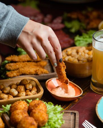 Foto de Woman dipping chicken croquette into sauce in beer setup with nuts - Imagen libre de derechos