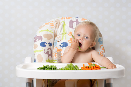 Photo for Baby girl sitting in a highchair eating raw, seasonal vegetables: carrots, beans, peas, celery - Royalty Free Image
