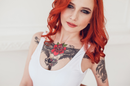 Photo for Portrait of a beautiful sexy girl with red hair and a tattoo. Woman with make-up and curls. - Royalty Free Image