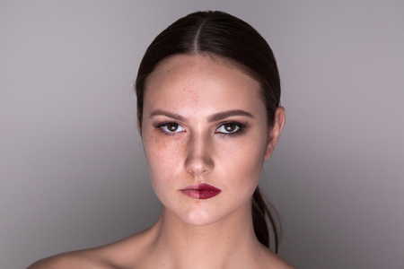 Woman with make-up on one side of the face and without make-up on the second side of the face. Before and after makeup.