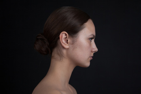 Profile of a womans face without makeup on a black background.
