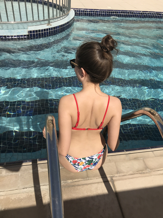 Photo for Back view of girl sitting near pool. - Royalty Free Image