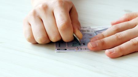 Foto de A hand scratching an instant lottery with coins - Imagen libre de derechos