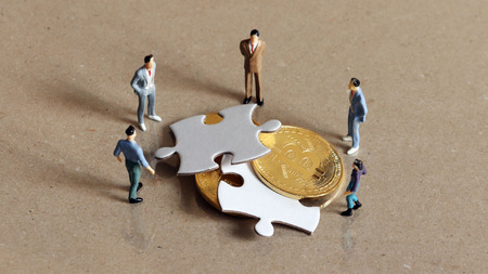Foto de Five miniature people staring down two pieces of the puzzle and bitcoin. - Imagen libre de derechos