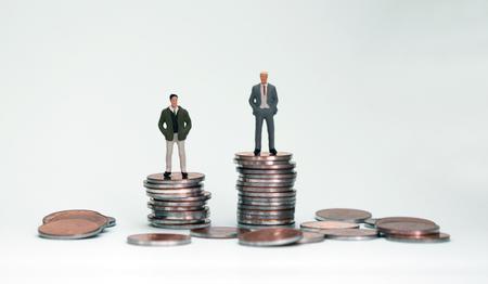 Photo pour Two miniature men on top of another pile of coins. - image libre de droit