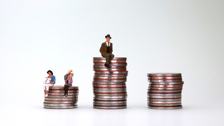 Photo for The source of the wage gap between men and women is analyzed. Pile of coins and a miniature woman holding a baby - Royalty Free Image