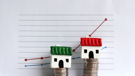 Photo for Housing price rising and differentiated concept. A miniature house on a pile of coins in front of a graph. - Royalty Free Image