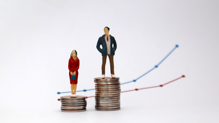 Photo for The concept of gender pay gap. A miniature man and a miniature woman standing on a pile of coins with a flow linear graph. - Royalty Free Image
