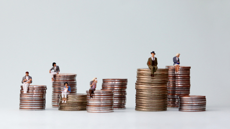 Photo for Miniature people standing on piles of different heights of coins. The concept of the income gap between individuals is not addressed. - Royalty Free Image