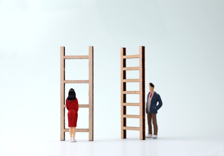 Photo for Miniature men and women standing in front of different ladders. The concept of gender differentiation between promotion and employment. - Royalty Free Image
